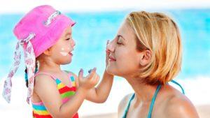 Criança passando protetor solar na mãe